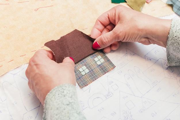 Primo piano del tessuto di cucitura della mano di una donna nella forma della casa su carta