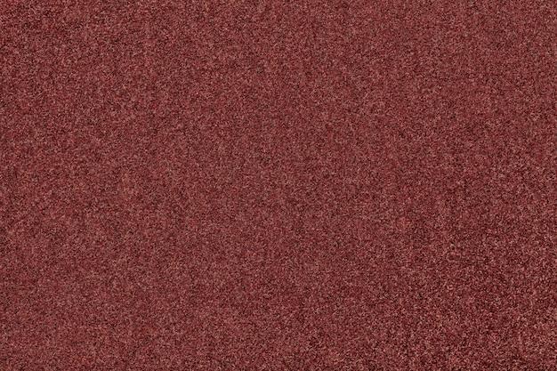 Primo piano del tessuto scamosciato opaco marrone scuro. texture di velluto di feltro di fondo