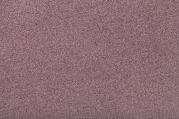 Primo piano del tessuto scamosciato opaco marrone scuro. texture vellutata di feltro.