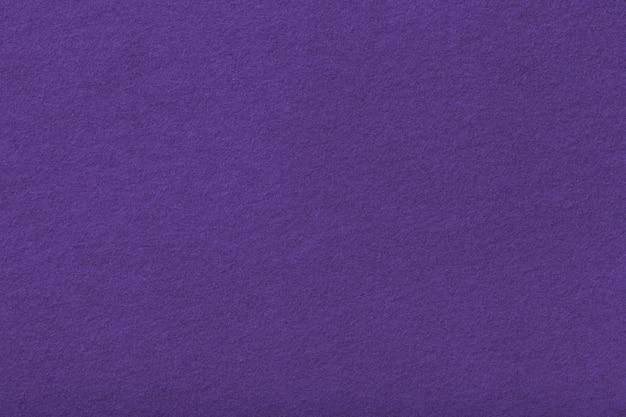 Primo piano del tessuto scamosciato opaco viola scuro. texture di velluto di feltro di fondo