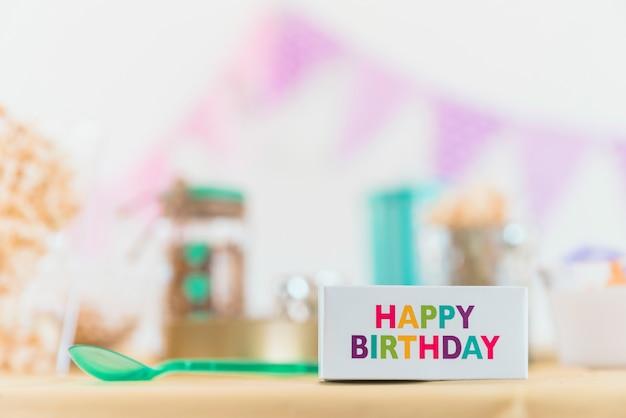 Primo piano del testo multicolore di buon compleanno sulla scatola con il cucchiaio