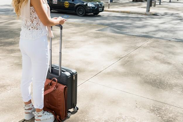 Primo piano del turista femminile che sta sulla borsa e sul passaporto di viaggio dei bagagli della tenuta della strada