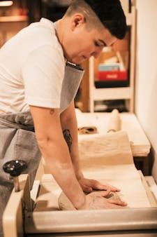 Primo piano del vasaio femminile che appiattisce l'argilla su carta con le mani