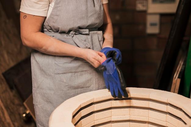 Primo piano del vasaio femminile che indossa i guanti blu nella fabbrica
