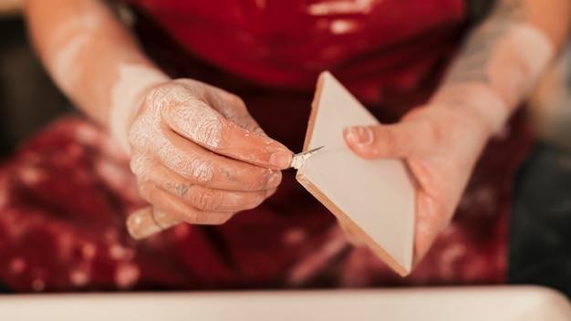 Primo piano del vasaio femminile che pulisce la pittura sulle mattonelle con lo strumento tagliente