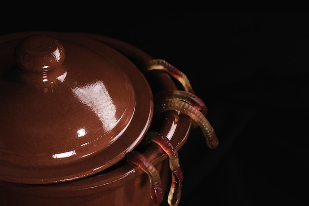 Primo piano del vaso marrone e dei vermi di gelatina