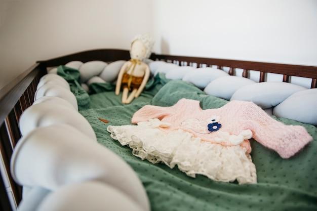 Primo piano del vestito da bambino con la bambola nella culla