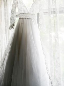 Primo piano del vestito da sposa bianco che appende dalla finestra