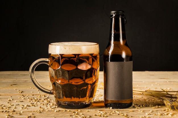Primo piano del vetro e della bottiglia alcolici con le orecchie di grano su superficie di legno