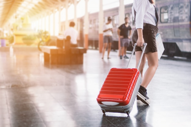 Primo piano del viaggiatore della giovane donna che porta la sua borsa rossa del carrello e mappa in una stazione ferroviaria.