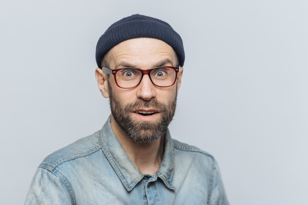 Primo piano del volto del bel maschio con la barba lunga con gli occhi azzurri, guarda con espressione sorpresa