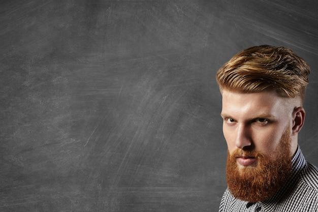 Primo piano del volto del coraggioso modello brutale giovane hipster con elegante barba rossa sfocata vestito con camicia a scacchi in posa all'interno nell'angolo inferiore destro della lavagna, dimostrando il suo taglio di capelli alla moda