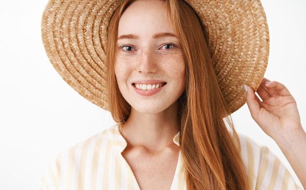 Primo piano del volto della ragazza affascinante felice della testarossa che gode della vacanza che sorride largamente che tiene il cappello di paglia sulla testa e che guarda con espressione felice e amichevole