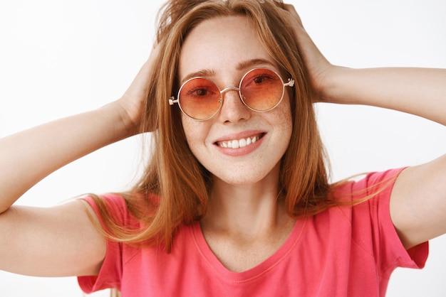 Primo piano del volto della ragazza allo zenzero attraente creativa e felice con graziose lentiggini in eleganti occhiali da sole rosa toccando l'acconciatura e sorridendo ampiamente godendo di un nuovo look mentre si guarda nello specchio soddisfatto, soddisfatto