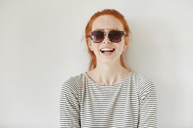 Primo piano del volto di felice bella donna alla moda giovane rossa che indossa occhiali da sole alla moda e top a maniche lunghe a righe, ridendo allegramente e divertendosi mentre posa