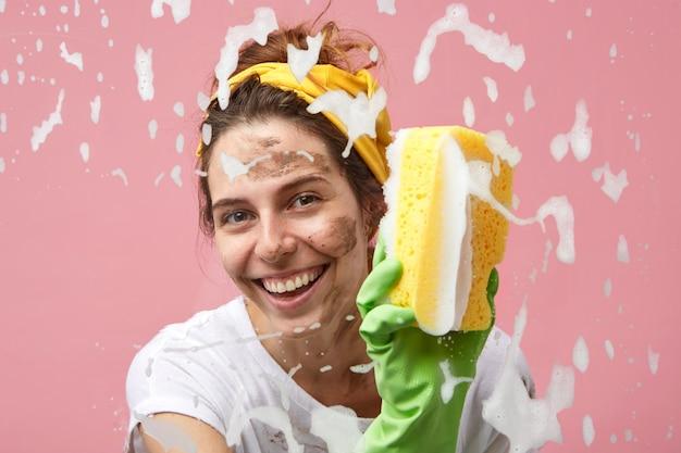 Primo piano del volto di felice bella giovane casalinga positiva con un sorriso affascinante finestra di lavaggio in cucina, spazzando via la schiuma spessa dalla superficie di vetro, godendosi il processo di pulizia, sorridente
