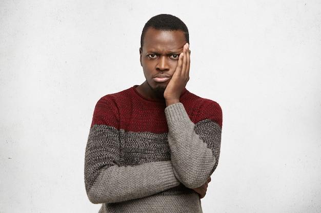 Primo piano del volto di giovane maschio nero frustrato infelice con espressione perplessa, tenendo la mano sulla sua guancia e tenendo le braccia conserte. triste uomo afroamericano vestito in maglione sentirsi annoiato o depresso