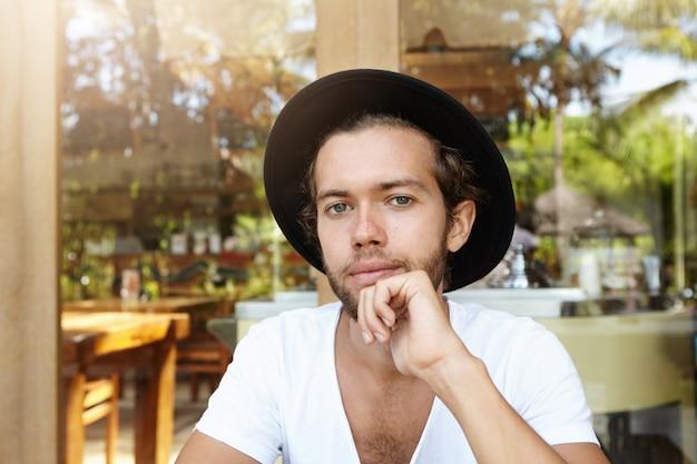 Primo piano del volto di giovane studente attraente alla moda con barba alla moda che indossa cappello nero e camicia con scollo a v guardando con un sorriso