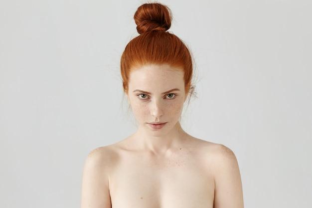 Primo piano del volto di un'affascinante giovane donna che indossa i capelli color zenzero nel nodo fissando con sguardo seducente, posa in topless al muro bianco, lentiggini che coprono il viso e le spalle.