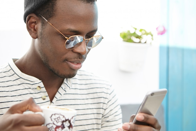 Primo piano del volto di un libero professionista dalla pelle scura che beve caffè o tè seduti in un ristorante all'aperto o in una caffetteria, indossando occhiali da sole alla moda a specchio