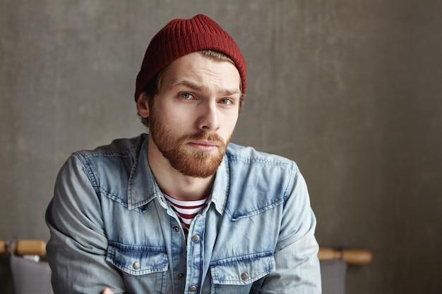 Primo piano del volto di un macho hipster con barba elegante che indossa cappello e camicia di jeans che guarda con espressione indecisa dubbiosa, frustrato e perplesso nel prendere decisioni importanti