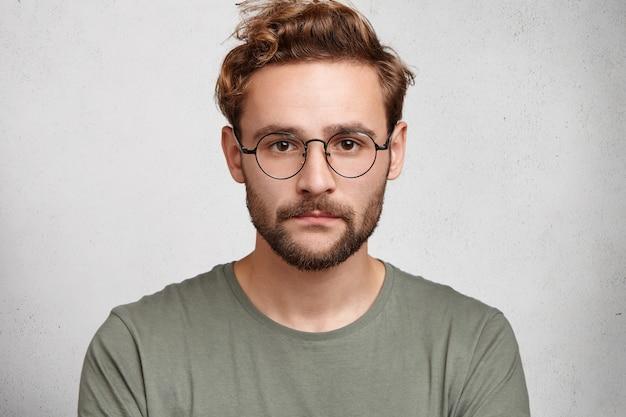 Primo piano del volto di un uomo barbuto serio con baffi e barba, indossa occhiali rotondi
