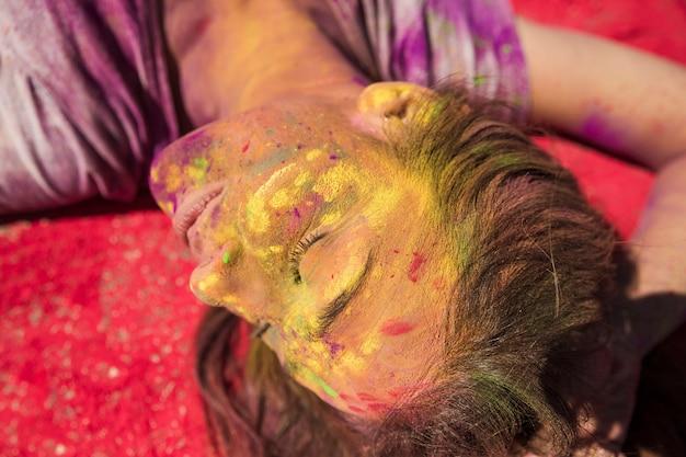 Primo piano del volto di una giovane donna coperto di colore holi