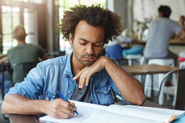 Primo piano del volto di uno studente laureato serio dalla pelle scura in camicia elegante blu che studia alla mensa o in uno spazio di coworking mentre si prepara per gli esami finali, prendendo appunti nel quaderno, avendo concentrato l'espressione