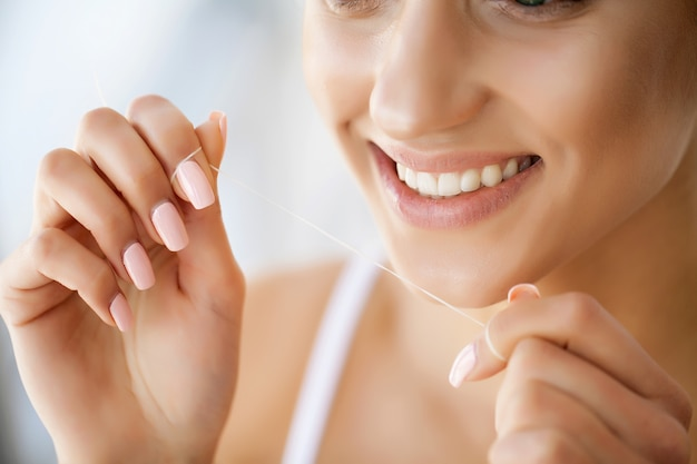 Primo piano del volto femminile con un sorriso perfetto. la ragazza sta pulendo i denti con filo speciale