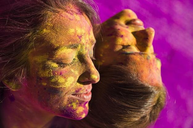 Primo piano del volto femminile ricoperto di colori holi multicolori
