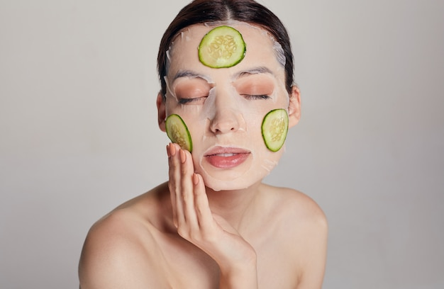 Primo piano delicata donna sofisticata in una maschera idratante con un cetriolo fresco sul viso nella bellezza seria con gli occhi chiusi e la mano destra vicino al viso