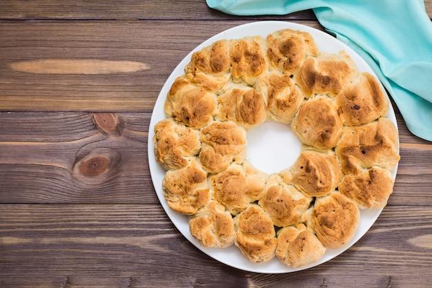 Primo piano delizioso del pane della scimmia su un piatto e su un tovagliolo su una tavola di legno