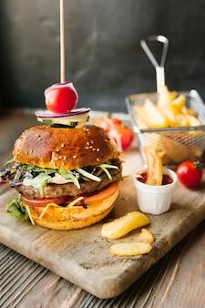 Primo piano dell'angolo alto dell'hamburger e delle fritture sul bordo di legno