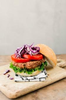Primo piano dell'angolo alto dell'hamburger sul bordo di legno