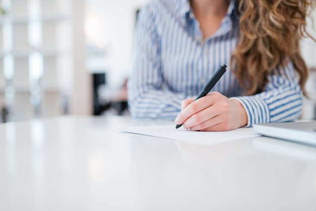 Primo piano dell'assistente amministrativo femminile che nota i dati, spazio della copia, vista frontale.