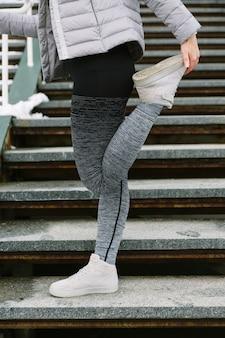 Primo piano dell'atleta femminile che allunga la sua gamba sulla scala