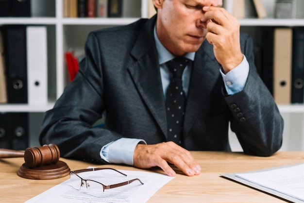 Primo piano dell'avvocato maturo maschio esaurito che si siede davanti allo scrittorio