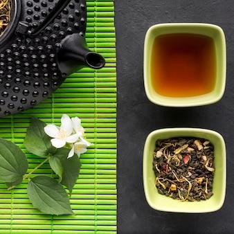 Primo piano dell'erba secca del tè e del fiore bianco del gelsomino