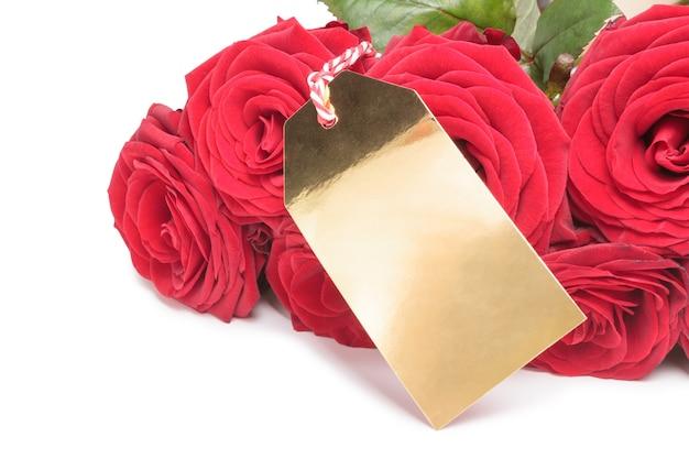 Primo piano dell'etichetta dorata in bianco con le rose rosse su fondo bianco. concetto di san valentino
