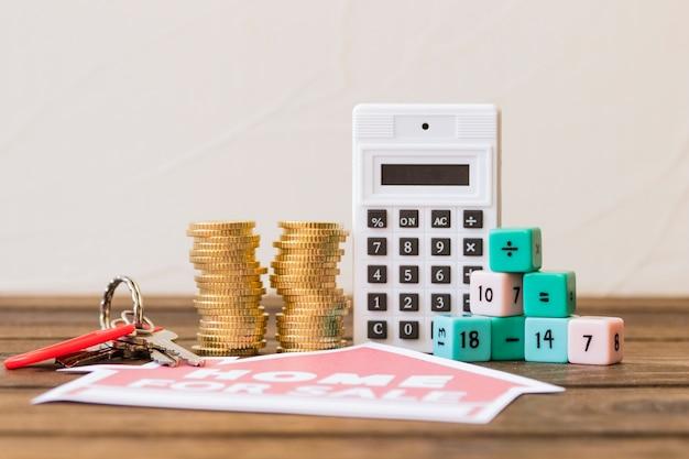 Primo piano dell'icona di vendita per la vendita con chiave, blocchi impilati di monete, calcolatrice e matematica