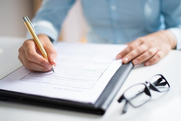 Primo piano dell'imprenditore che fa le note nel documento