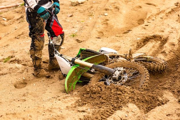 Primo piano dell'incidente nella corsa di mountain bike nella pista di sporcizia con detriti volanti durante un'accelerazione