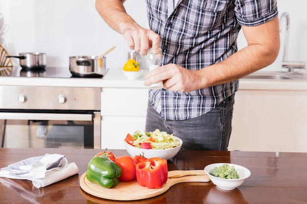 Primo piano dell'insalata di condimento della mano di un uomo con sale marino fresco nella cucina