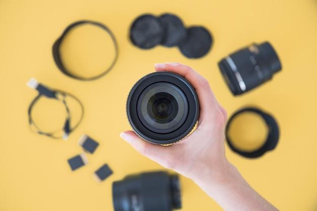Primo piano dell'obiettivo della fotocamera della mano della persona sopra gli accessori della macchina fotografica su fondo giallo