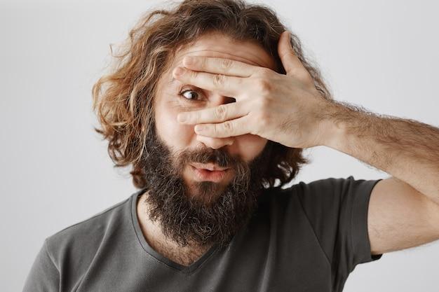 Primo piano dell'uomo barbuto eccitato mediorientale che dà una occhiata curiosa attraverso le dita
