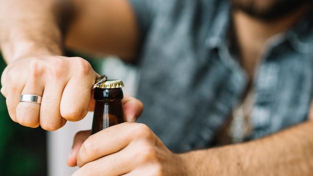 Primo piano dell'uomo che apre il cappuccio della bottiglia con l'apri