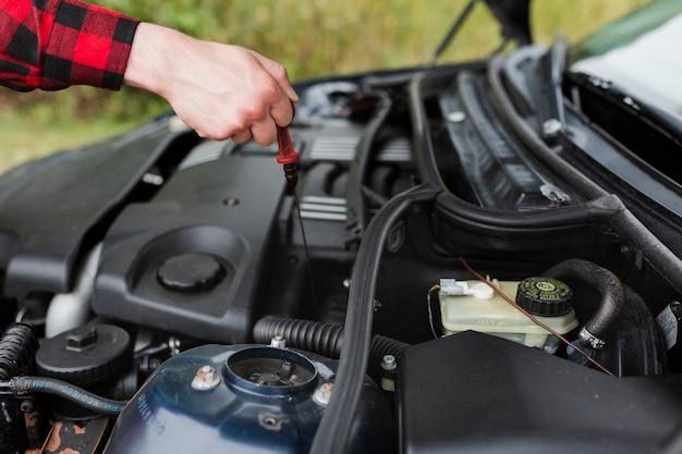 Primo piano dell'uomo che controlla olio per motori
