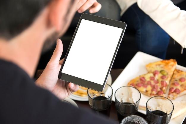 Primo piano dell'uomo che esamina compressa digitale in bianco