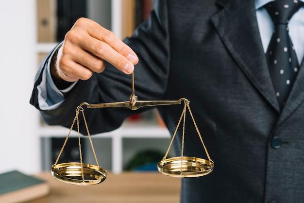 Primo piano dell'uomo che giudica la bilancia della giustizia dorata a disposizione