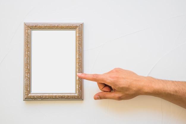 Primo piano dell'uomo che indica alla cornice dorata bianca sulla parete